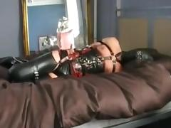 Rubber girl harnessed and hogtied